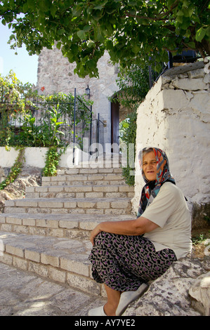 Old woman sitting at entrance to Marmaris Castle in Marmaris, TURKEY - Stock Photo