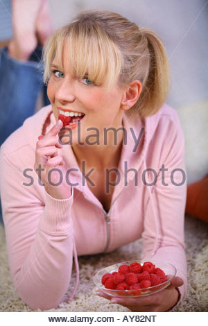 woman eating a raspberry lying on a carpet - Stock Photo