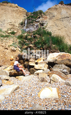 Woman looking at a waterfall on the beach in Hastings Country Park Hastings East Sussex England South Coast Britain - Stock Photo