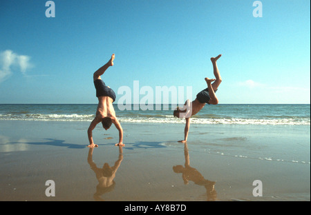 Two boys doing handstands on the beach Camber Sands East Sussex UK - Stock Photo