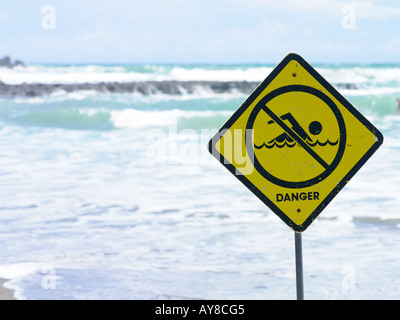 warning sign to surfers and swimmers at piha beach with surf in background on a blue sunny summers day - Stock Photo