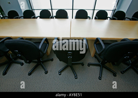 Rows of empty conference room chairs in highrise office building - Stock Photo