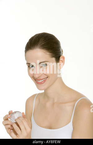 Woman using nail brush, smiling at camera - Stock Photo