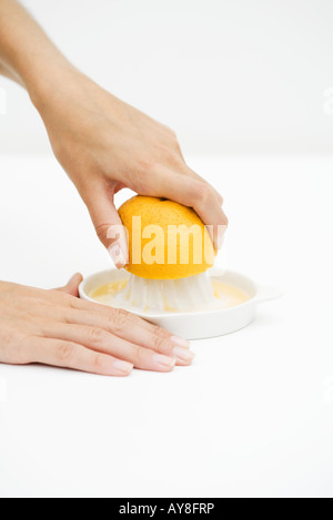 Woman squeezing orange with citrus press, cropped view of hands - Stock Photo
