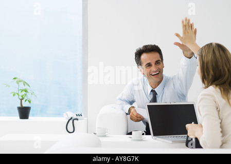 Business associates giving each other high-five in office - Stock Photo
