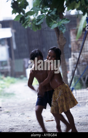 Two young Gilbertese girls play in a refreshing tropical downpour. Tarawa, Kiribati. - Stock Photo
