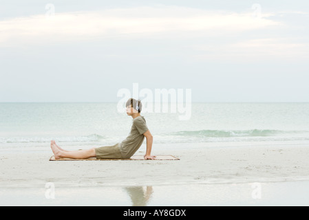 Teenage boy sitting on the beach, listening to headphones, side view - Stock Photo