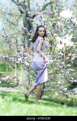 Young woman in dress walking in meadow, looking over shoulder, low angle view - Stock Photo