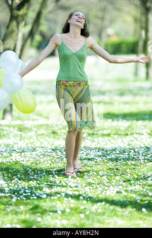 Young woman walking in meadow, holding balloons, arms out, smiling - Stock Photo