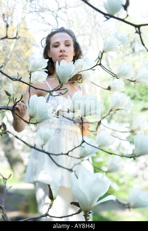 Young woman standing among flowering tree, looking at camera - Stock Photo
