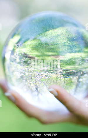 Woman holding glass ball in hand outdoors, extreme close-up - Stock Photo