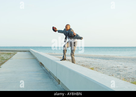Businessman standing on low wall at the beach, arms out, holding football - Stock Photo
