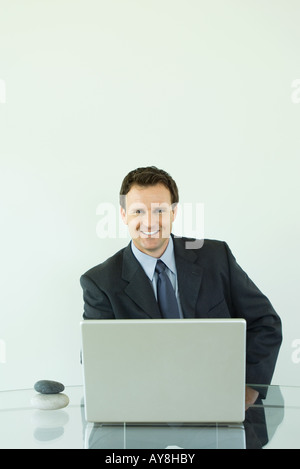 Businessman using laptop computer, smiling at camera, pebbles stacked on desk next to him - Stock Photo