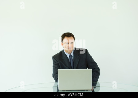 Businessman sitting at desk, using laptop computer, smiling at camera - Stock Photo