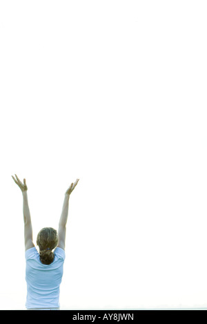 Teenage girl with arms raised, rear view - Stock Photo