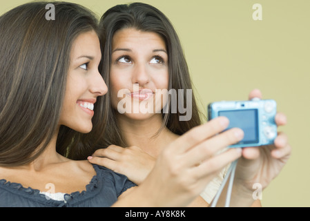 Teenage girl photographing self and twin sister with digital camera, both looking away, close-up - Stock Photo