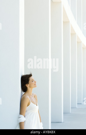 Woman leaning against column, eyes closed, hair tousled by breeze - Stock Photo