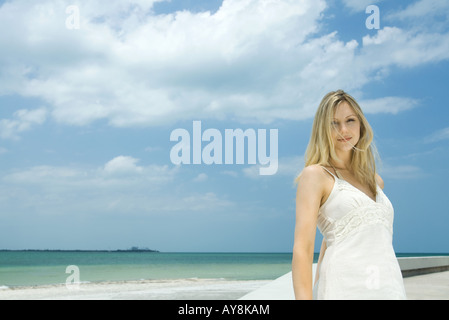 Young woman standing by the beach, hair tousled by wind, smiling at camera - Stock Photo