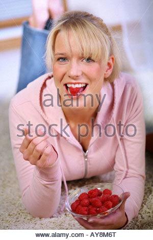 woman eating raspberries lying on the floor - Stock Photo