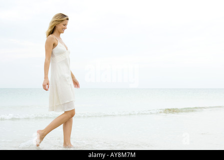 Young woman in sundress walking in surf at beach, smiling, full length - Stock Photo