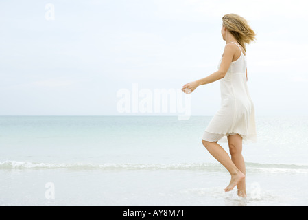 Young woman in sundress walking in shallow water at beach, looking toward horizon - Stock Photo