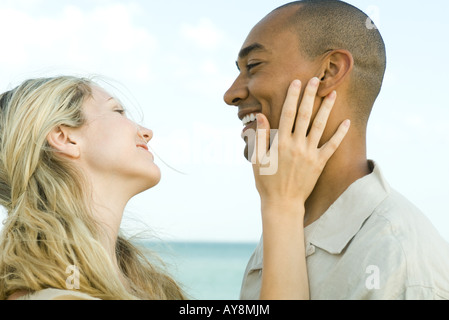 Couple smiling at each other, woman's hand on man's cheek, side view - Stock Photo