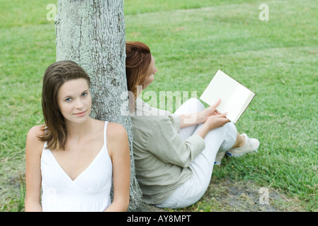 Mother and daughter leaning against tree trunk, woman reading book, teen girl smiling at camera - Stock Photo