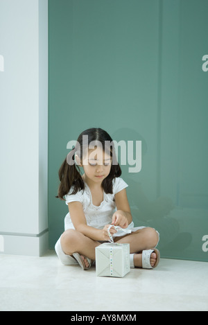 Little girl sitting on the ground, tying ribbon on gift - Stock Photo