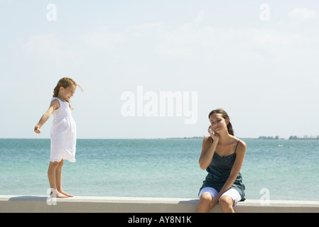 Little girl standing on low wall, watching older sister using cell phone - Stock Photo