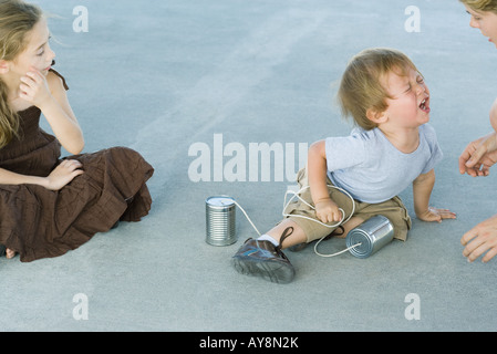 Little boy holding tin can phone, having tantrum, mother and sister watching - Stock Photo