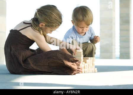 Brother and sister sitting on the ground, stacking building blocks together - Stock Photo