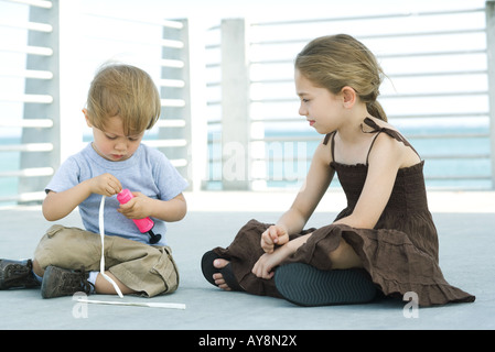 Little boy sitting on the ground inflating balloon with air pump, older sister watching - Stock Photo