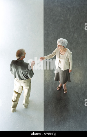 Couple standing on divided black and white floor, woman holding hand out in greeting, high angle view - Stock Photo