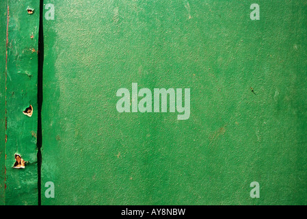 Green painted surface with holes, close-up, full frame - Stock Photo