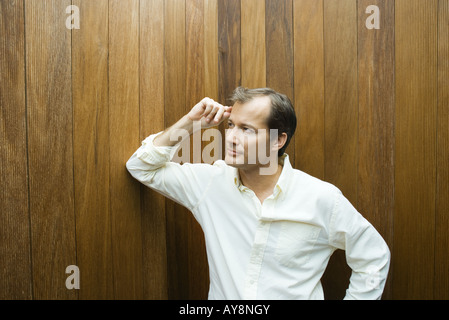 Man leaning elbow against wall, hand on head, looking away - Stock Photo