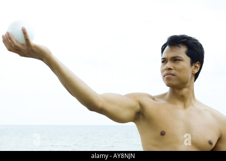 Man at the beach with arm raised, looking at ball in hand, close-up - Stock Photo