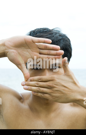 Man with hands raised, looking through finger frame at camera - Stock Photo
