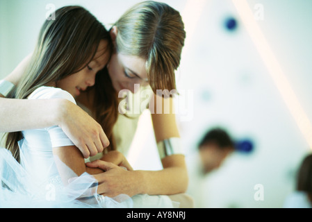 Mother embracing daughter, both looking down, close-up - Stock Photo