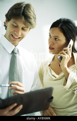 Male and female colleagues standing side by side, woman using cell phone, man looking at binder - Stock Photo