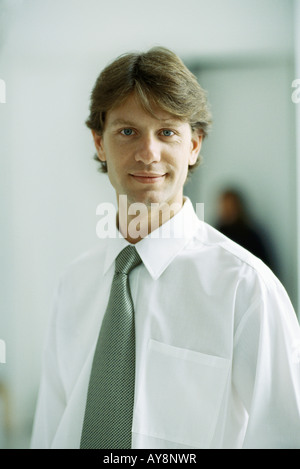 Businessman smiling at camera, portrait - Stock Photo