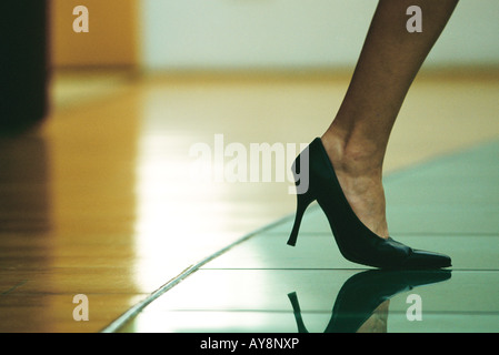 Woman walking in high heels, cropped view of foot - Stock Photo