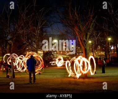 The nightfall firedancers in the Kaisaniemi park, Helsinki, Finland, Europe. - Stock Photo