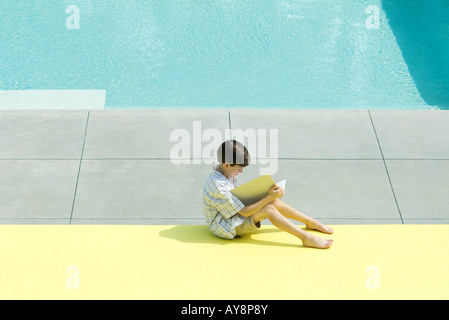 Boy sitting next to swimming pool, reading book, high angle view - Stock Photo
