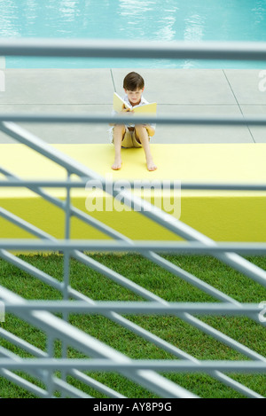 Boy sitting by swimming pool, reading book, viewed through railing - Stock Photo