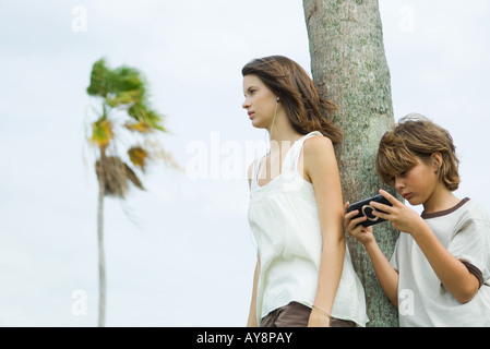 Siblings leaning against tree trunk, boy playing handheld video game, teen girl listening to earphones - Stock Photo