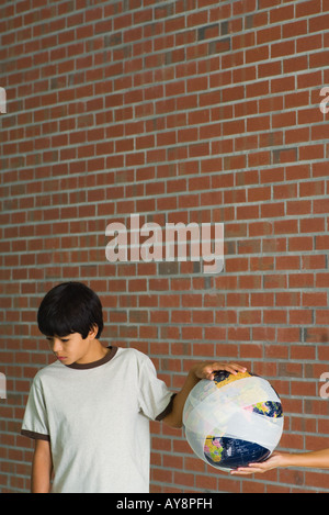 Woman handing boy globe wrapped in bandages, boy looking down, cropped view - Stock Photo
