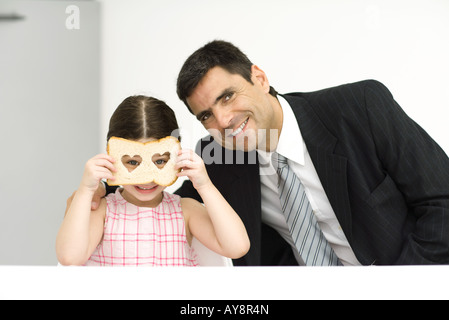 Father and daughter sitting side by side, girl looking through slice of bread with heart-shaped holes, both smiling - Stock Photo