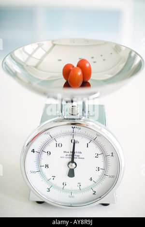 Three cherry tomatoes on weight scale, close-up - Stock Photo