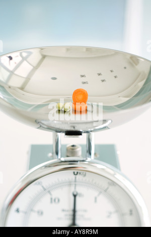 Capers and carrot slices on weight scale, close-up - Stock Photo