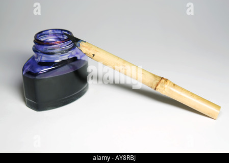 Reed pen and bottle of indigo ink, close-up - Stock Photo